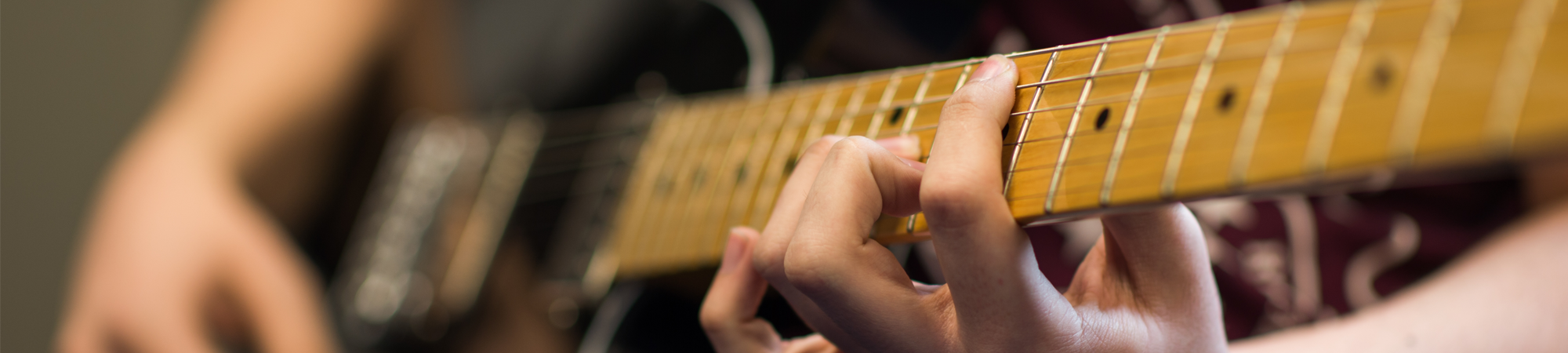 Picture of a student playing the guitar